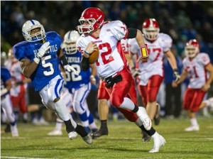 St. John's High School quarterback Drew Smiley (#12) breaks for a long run as Leominster High School's Jarell Addo (#5) scrambles in hot pursuit.