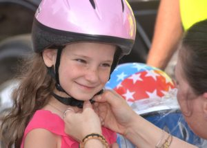 Rylie Jordan, 7, gets fitted for a free bicycle helmet.