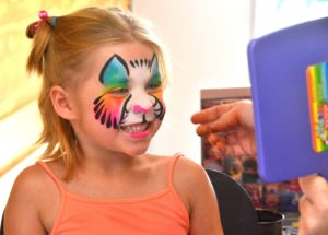 Shaylynn Gifford, 6, happily views her face painted as a rainbow kitty inside the Grafton mobile command unit.
