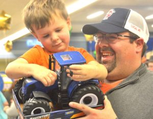 Caleb Gilchrist, 2, gets a toy tractor as well as a lift from his dad, Brendon.