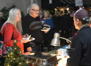 Linda and Dickie Bolt are served rolled stuffed turkey breast with bacon by Dan Mauro of The Buffet Way.
