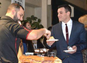 Mike Lombardi of The Vin Bin serves a slice of muffuletta sandwich to Kevin Kaselouskas.