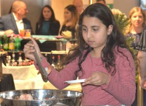 Olivia Soliman, 12, gets shrimp from the raw bar sponsored by St. Mary's Credit Union.