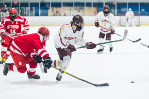 Algonquin's Ben Cotter and Hudson's Jacob Leonardo scramble for a loose puck. Algonquin defeated Hudson in this game on January 27.