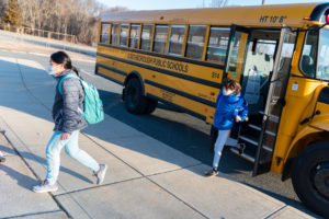 Students jump off their school bus outside Southborough's Neary Elementary School.