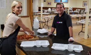 Sophie Plouffe and Mike Wickstrom help hand out meals at the Peace of Bread Food Pantry.