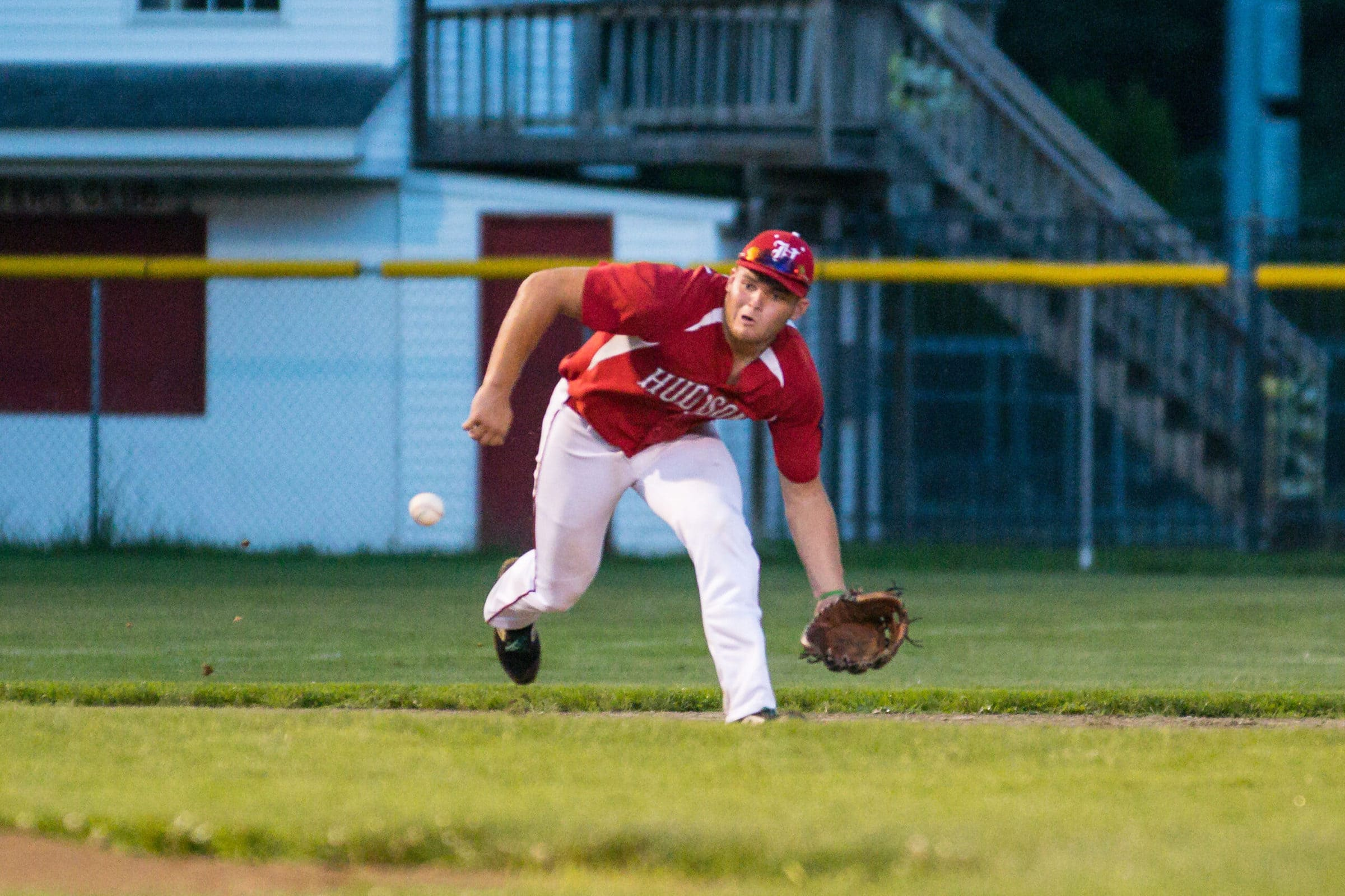 A Hudson player charges forward to corral a ground ball.