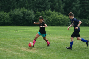 A young soccer player charges forward with the ball as a defender chases her.