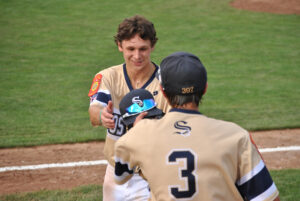 A Shrewsbury player hands a hat to his teammate.