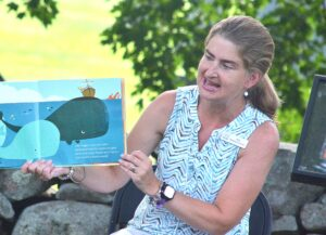 Children's Librarian Kim Ivers, aka Miss Kim, reads a pirate-themed children's book at the July 7 session of Outdoor Story Time on the lawn of the Southborough Library.