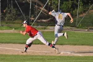 An opponent lunges to tag first base to beat a throw during a recent game. Northborough Legion Post 234 won the game 3-1.