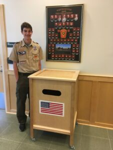 Justin Cappuccio stands next to the box he made to dispose of and retire American Flags.