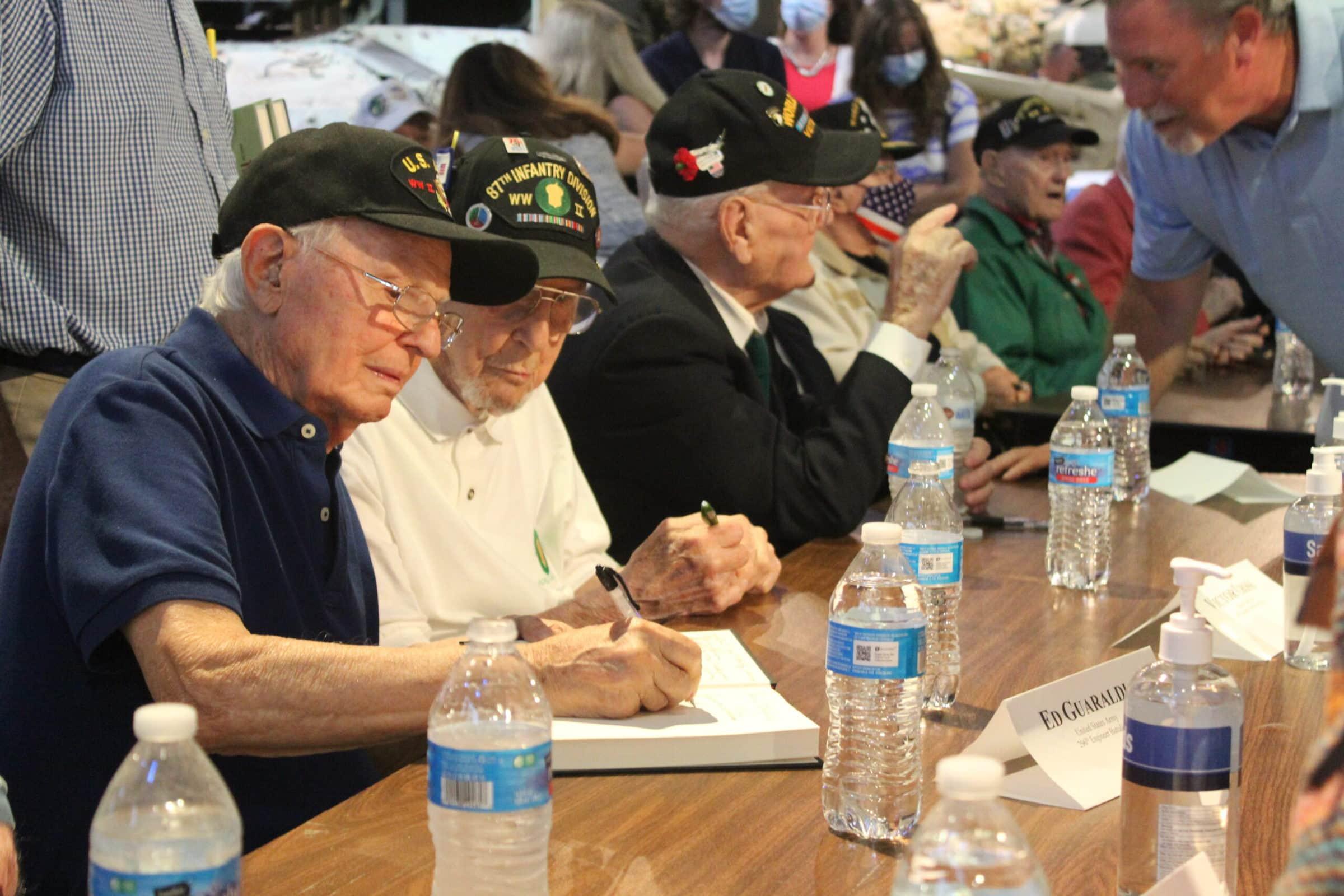 Veterans sign books.