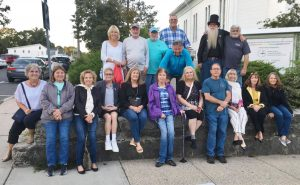 """Members of the Hudson High School Class of 1971 followed their """"Sit on the Wall"""" tradition on Main Street, during their recent 50th reunion weekend. Photo/Courtesy Stephen McCarthy"""