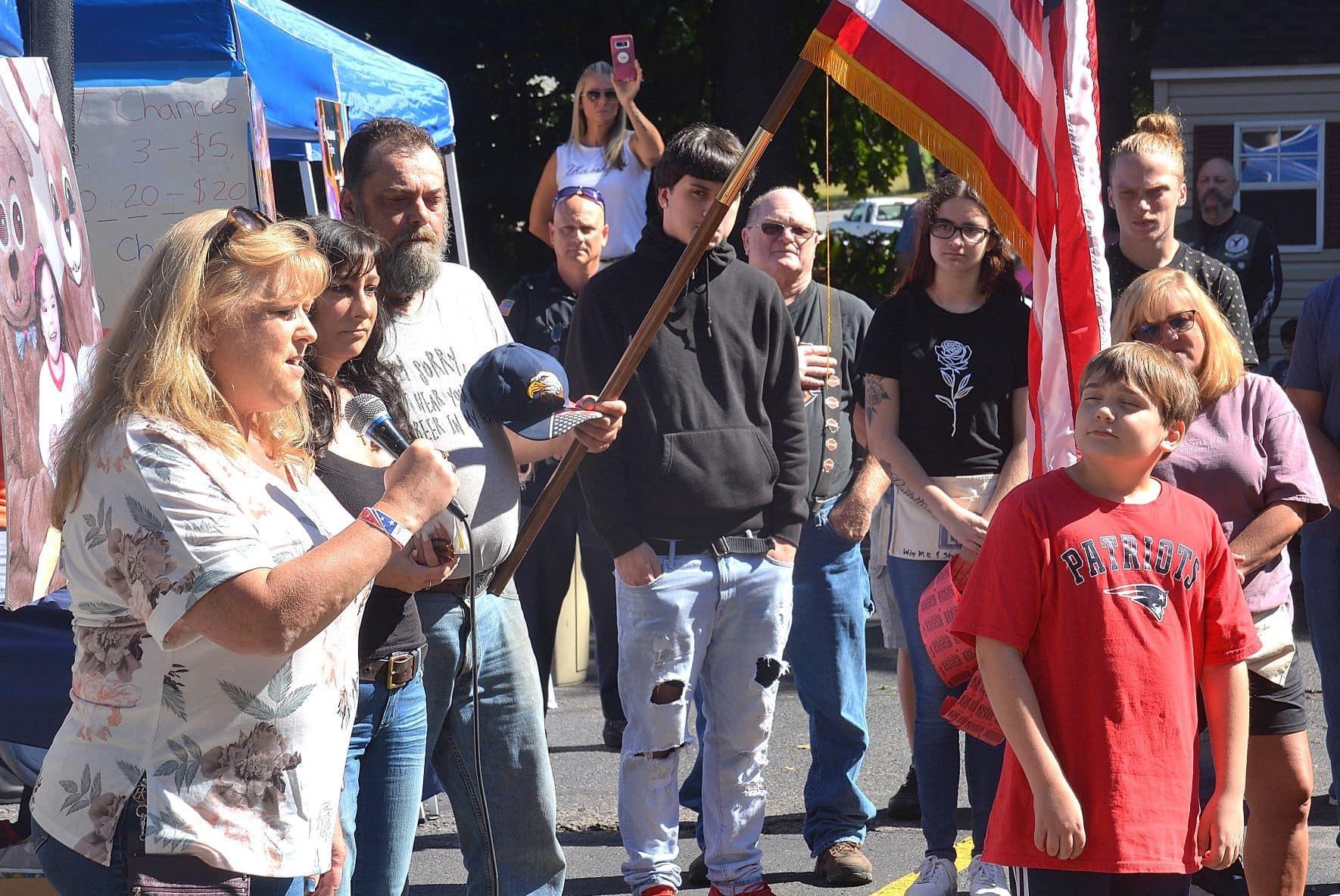 """Meg Deane (far left) sings the national anthem. Ryan Roderick, 10, (far right) had recited """"The Pledge of Allegiance."""""""