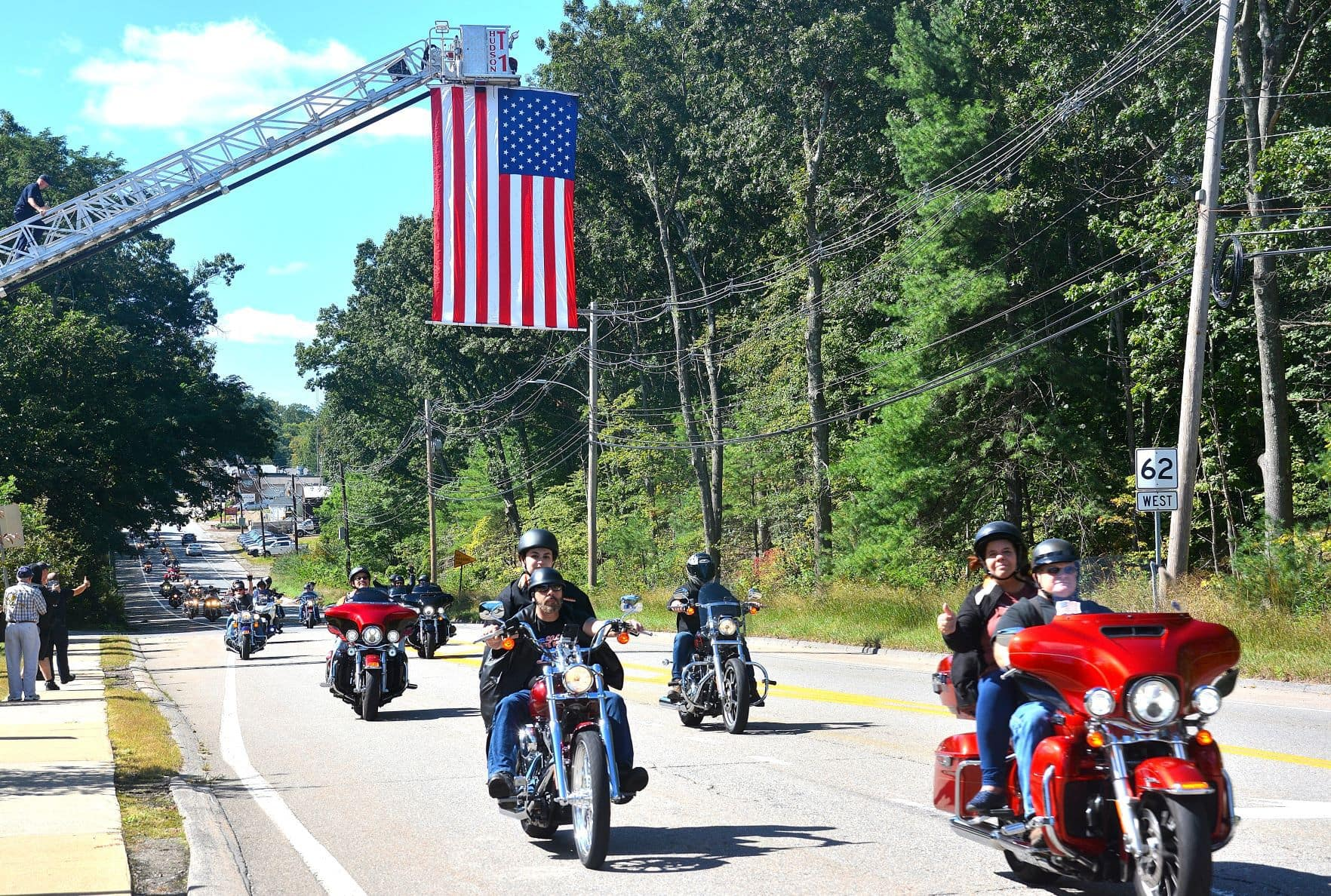 An American flag hoisted over Coolidge Street by the Hudson Fire Department welcomes the ride participants back to Hudson, including event co-founders Lenore and John Musorofiti (far right).