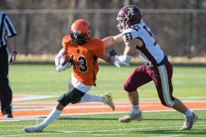 A Marlborough football player fights to turn a corner against an Algonquin defender during the Fall II football season earlier this year.  (Photo/Jeff Slovin)