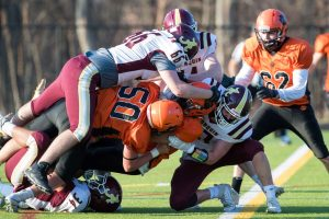 Marlborough football players fall to the ground amid a pile of Algonquin defenders.  Photos/Jeff Slovin