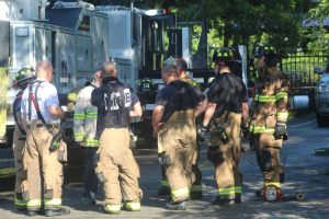 Firefighters gather after battling a fatal fire in Northborough on Sept. 10.   Photo/Laura Hayes