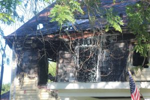 Water pours off the roof at 129 Maple St. in Northborough during a fatal fire on Sept. 10.
