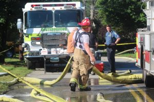 Firefighter organize hoses as they wind down their response to a fatal fire in Northborough on Sept. 10.