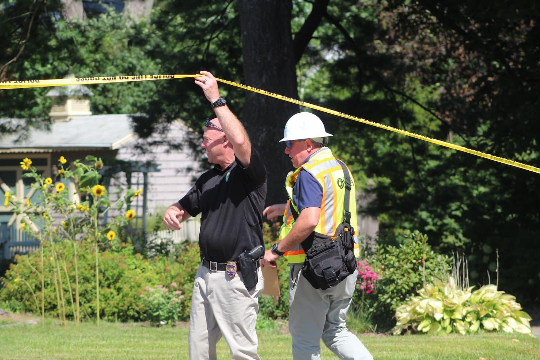 An OSHA worker ducks under police tape. (Photo/Laura Hayes)