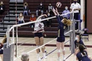 A Westborough girls volleyball player sets a ball for her teammate to spike.