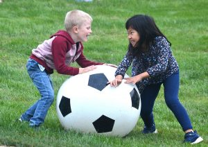 Conrad Smith, 4-1/2 and Elena Wang, 5, play with a jumbo soccer ball.