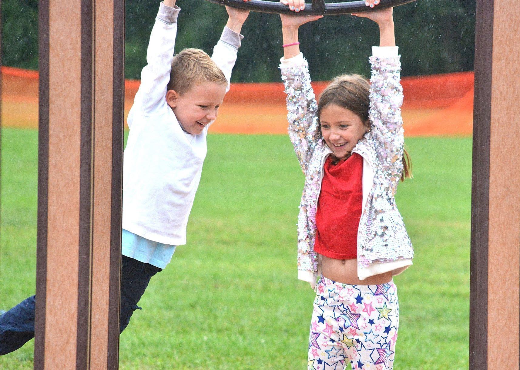 The Stucka siblings – Bradley, 5, and Hayden, 9 – swing together on monkey bars.