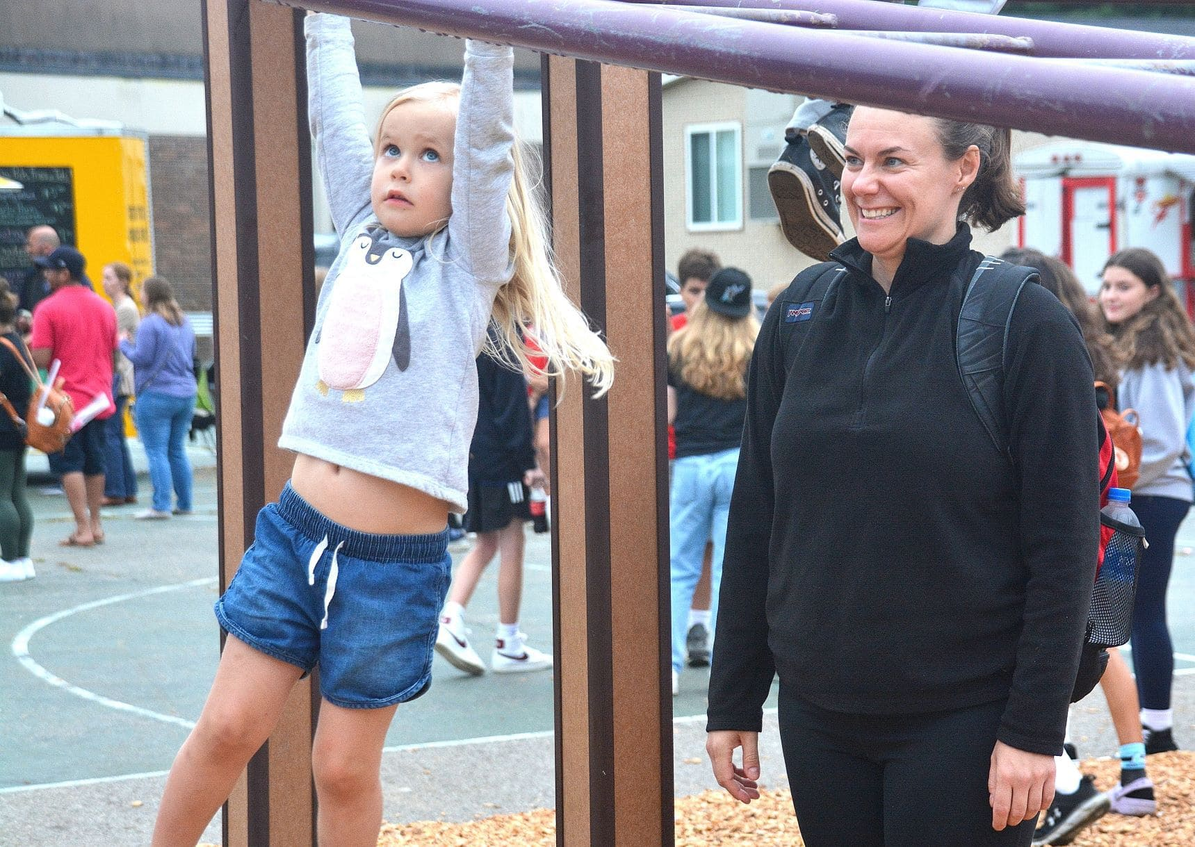 Ava Tumeinski, 3, tries her hand on monkey bars with her mother Jen nearby in case assistance is needed.