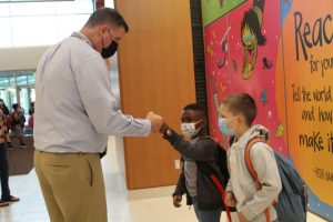Superintendent Joseph Sawyer fist bumps a student.