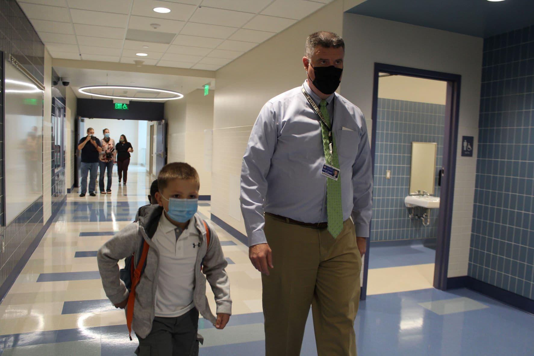 Superintendent Joseph Sawyer walks students to their new classroom.