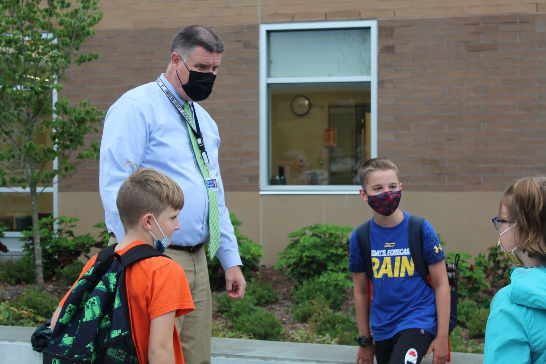 Superintendent Joseph Sawyer greets children who walked to school.
