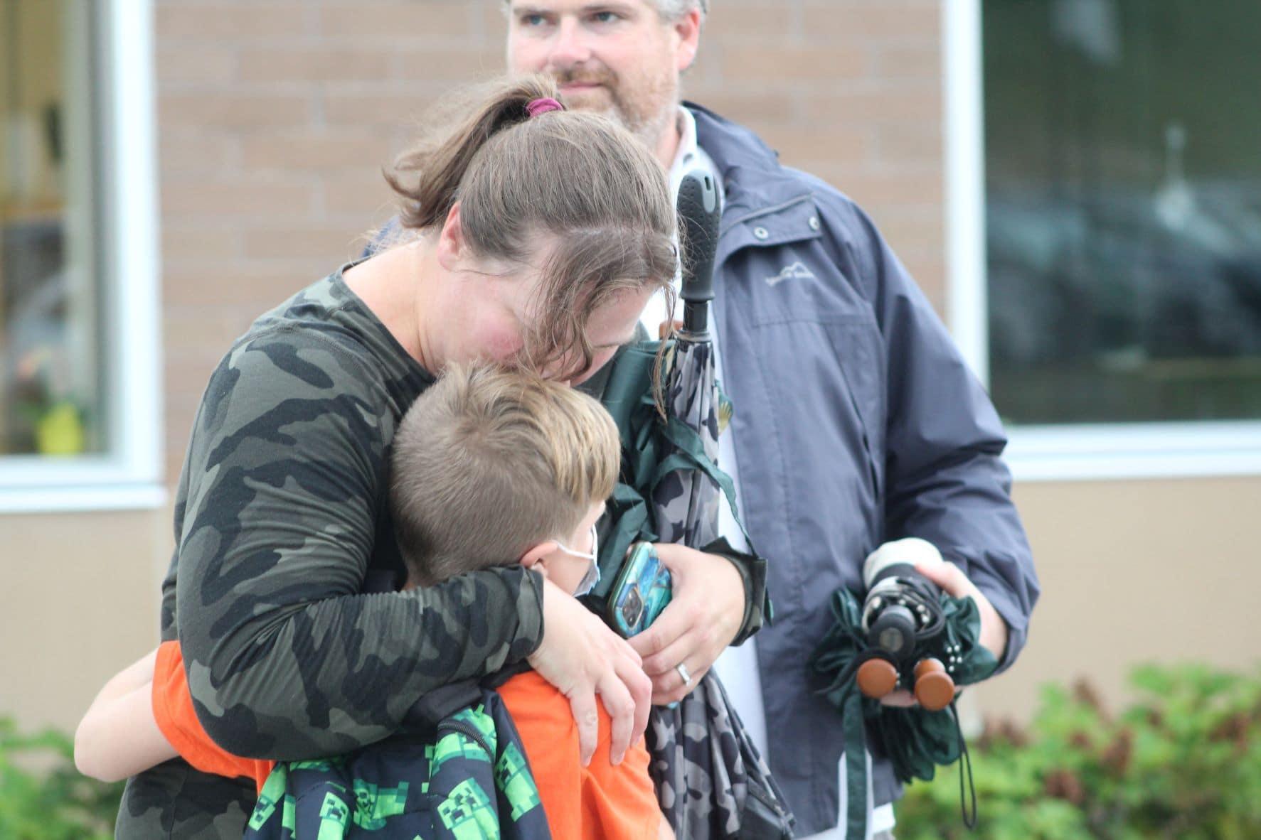 Parent Michelle Conlin hugs her son Garrett.