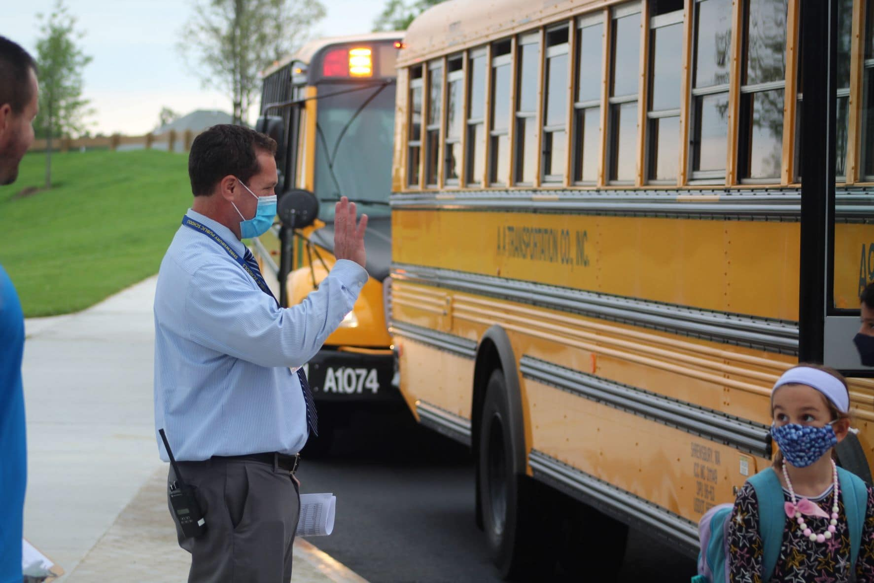 Principal Chris Girardi greets students as they come off the bus.