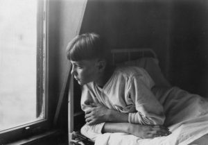 A boy looks wistfully out the bedroom window at the State Reform School for Boys.