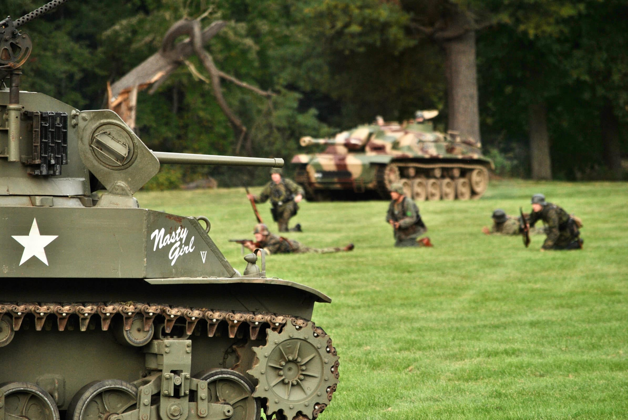 Reenactors line up in battle with an abandoned armored vehicle in the foreground.