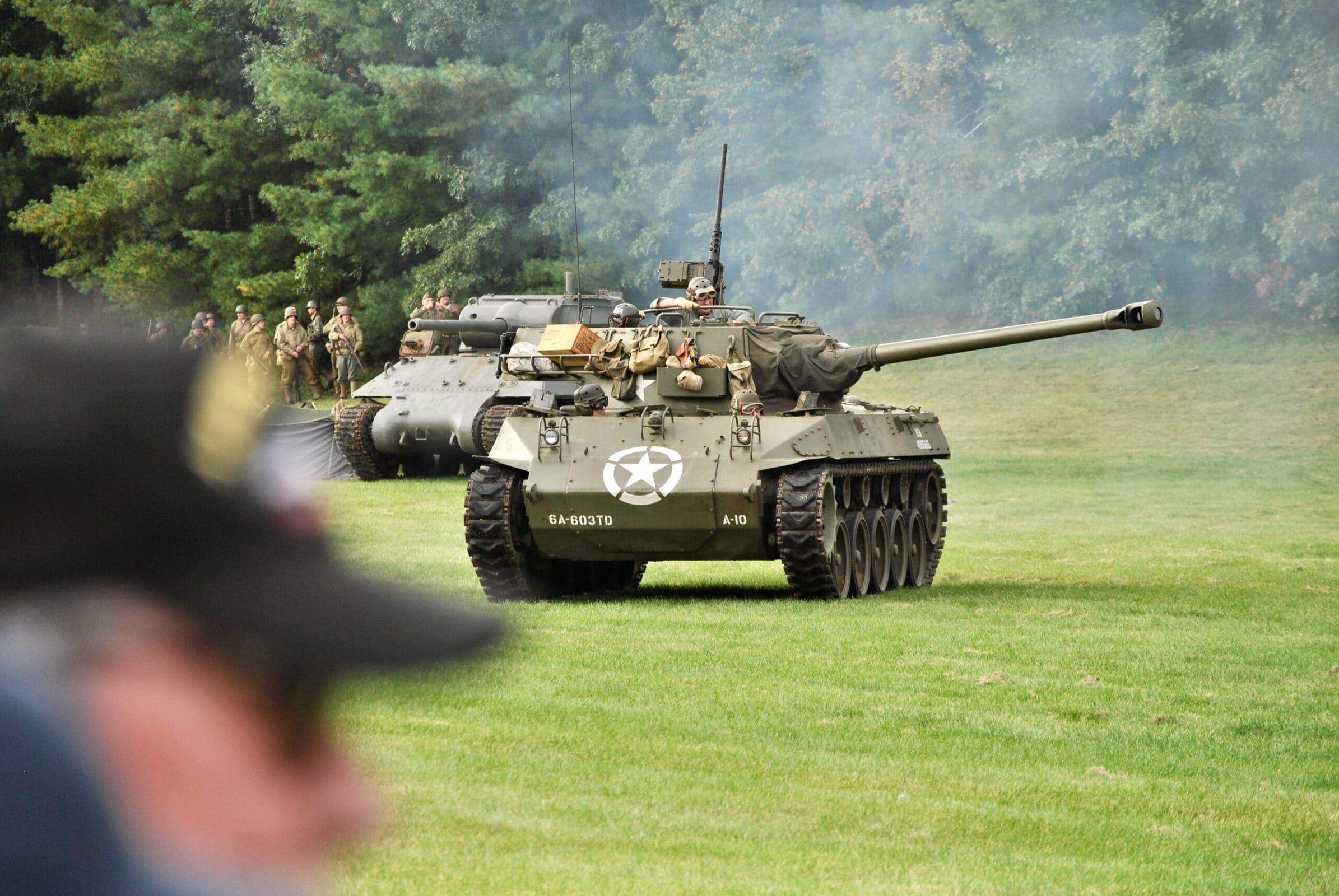 A tank swings its turret into position as reenactment attendees look on.