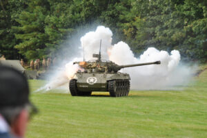 An explosion showers a tank in smoke, sparks and fire during this year's Battle for the Airfield reenactment.