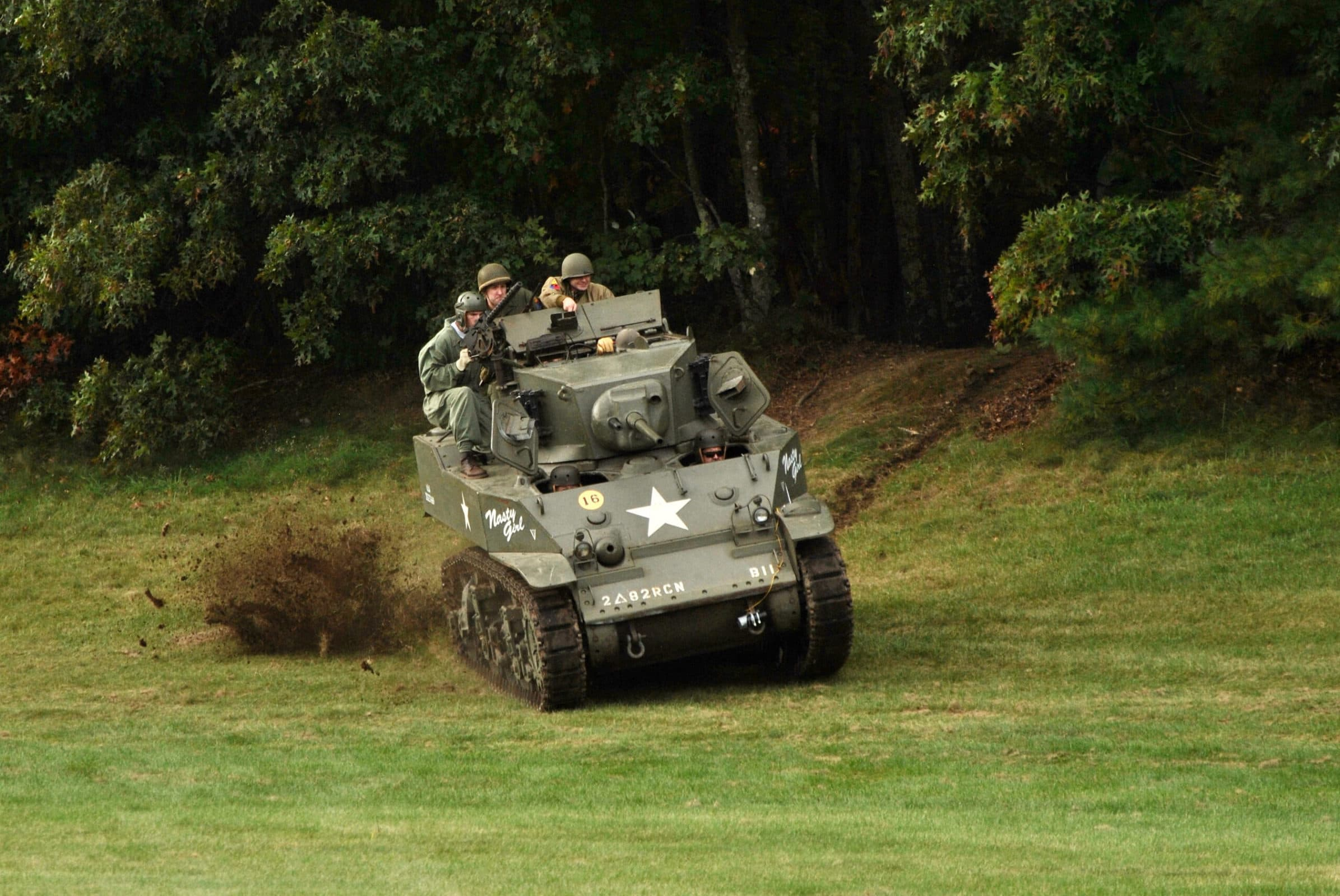 A tank tears out of the woods on the grounds of the American Heritage Museum in Hudson during this year's Battle for the Airfield World War II reenactment.