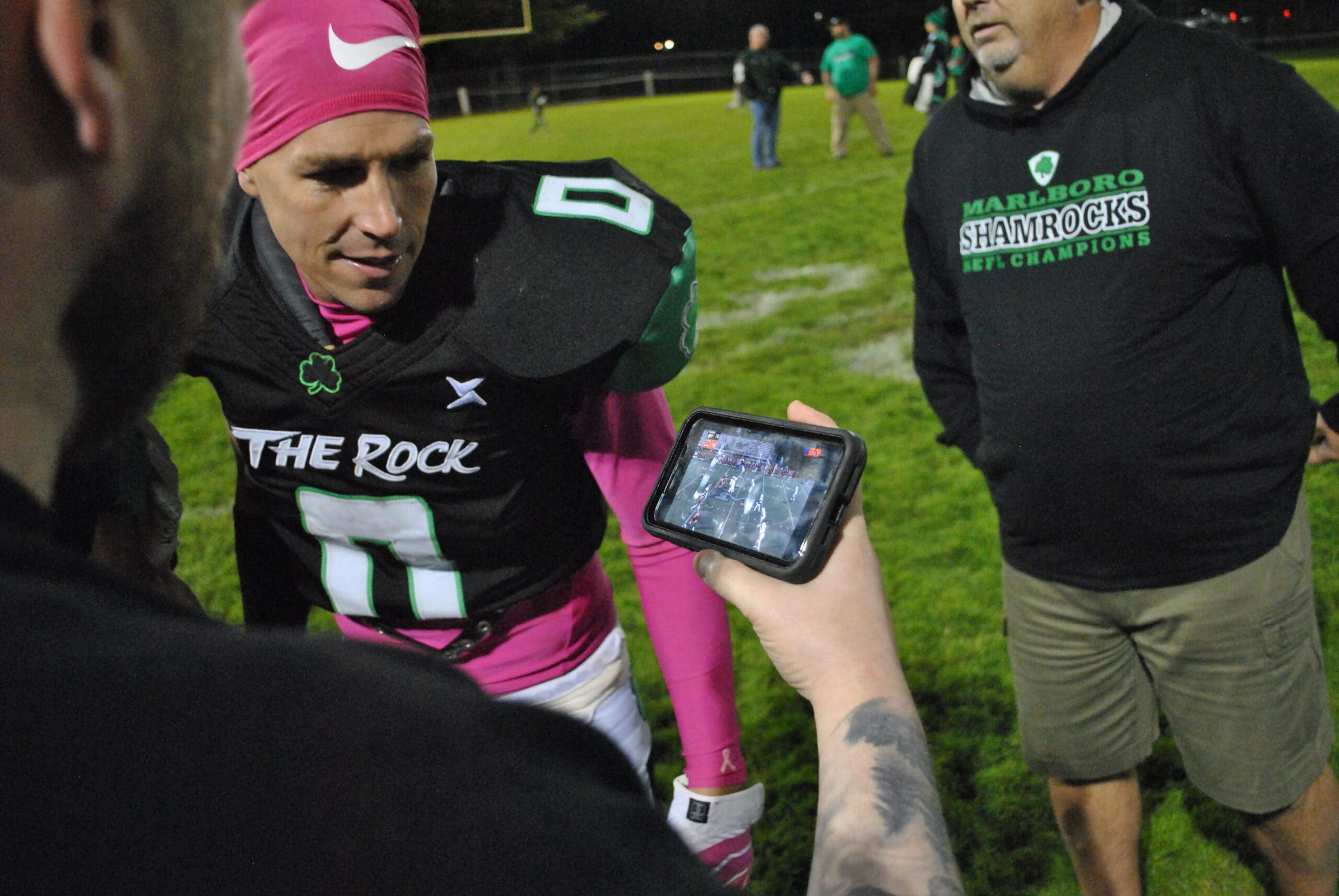 Shamrocks offensive coordinator Harrison Ingles watches a livestream on his phone after Marlborough's victory, Oct. 9, to see who the Shamrocks would face in the championship. Photos/Dakota Antelman