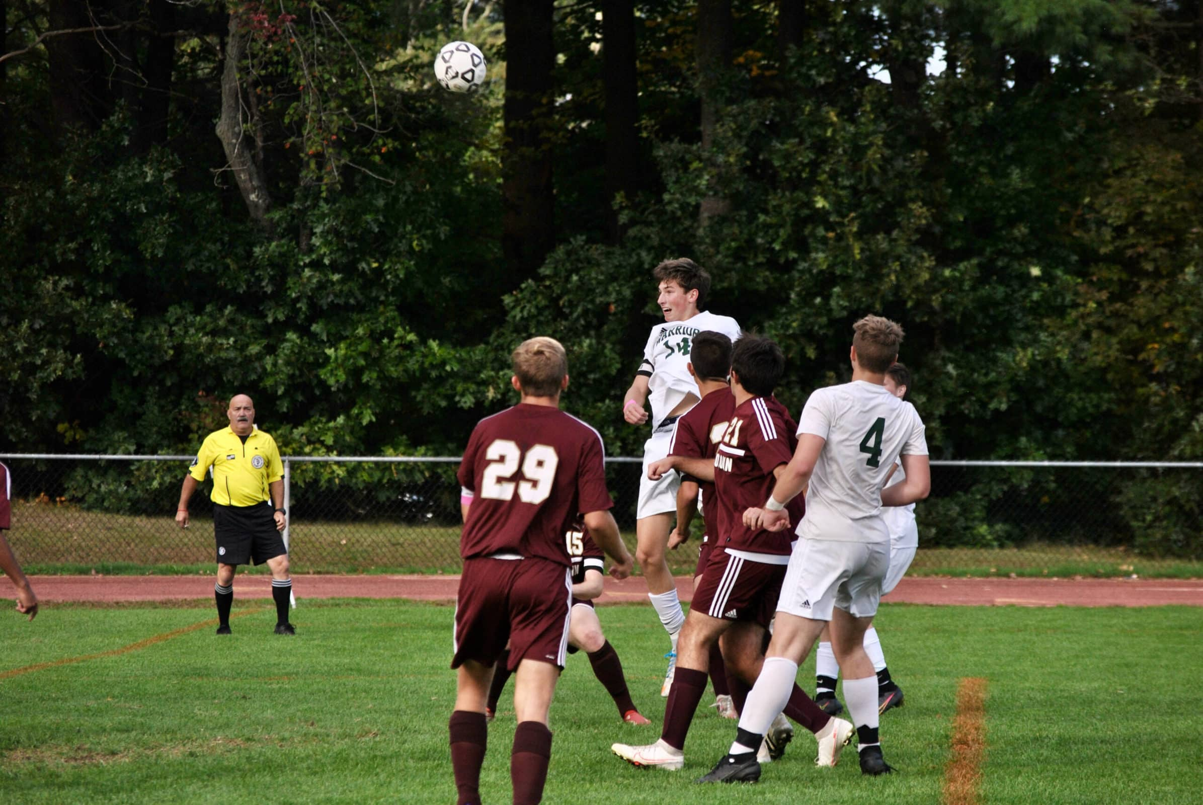 A Tantasqua player rises above Algonquin opponents to win a header towards the Algonquin goal.