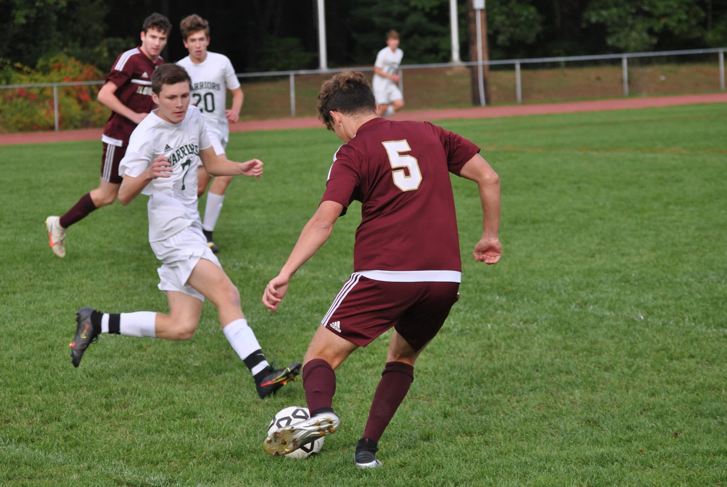 Algonquin's Jeremy Strauss passes the ball into open space ahead of a teammate as he is pursued by a Tantasqua opponent.