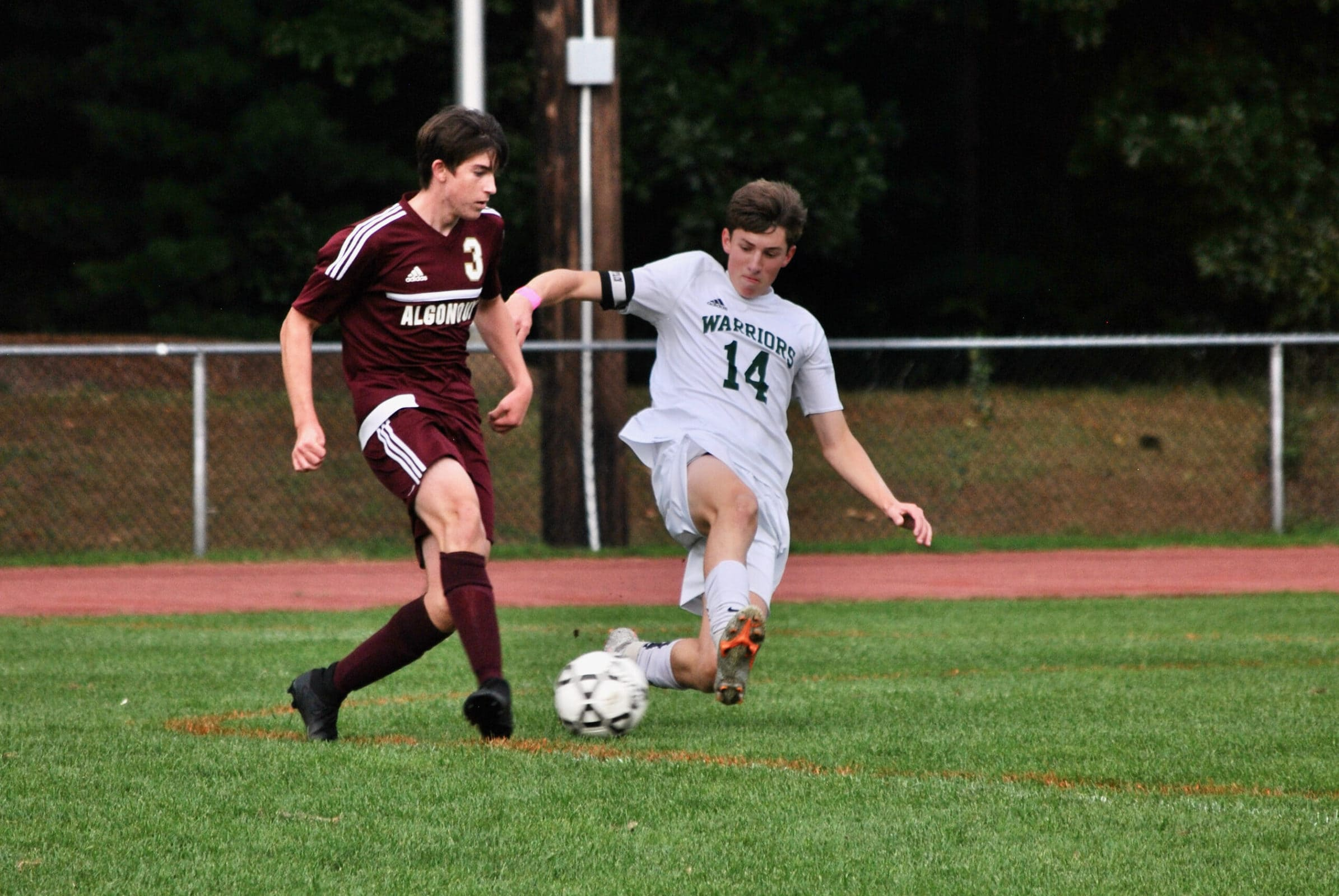 Algonquin's Conor Hoolahan maintains possession as a Tantasqua opponent executes a slide tackle.