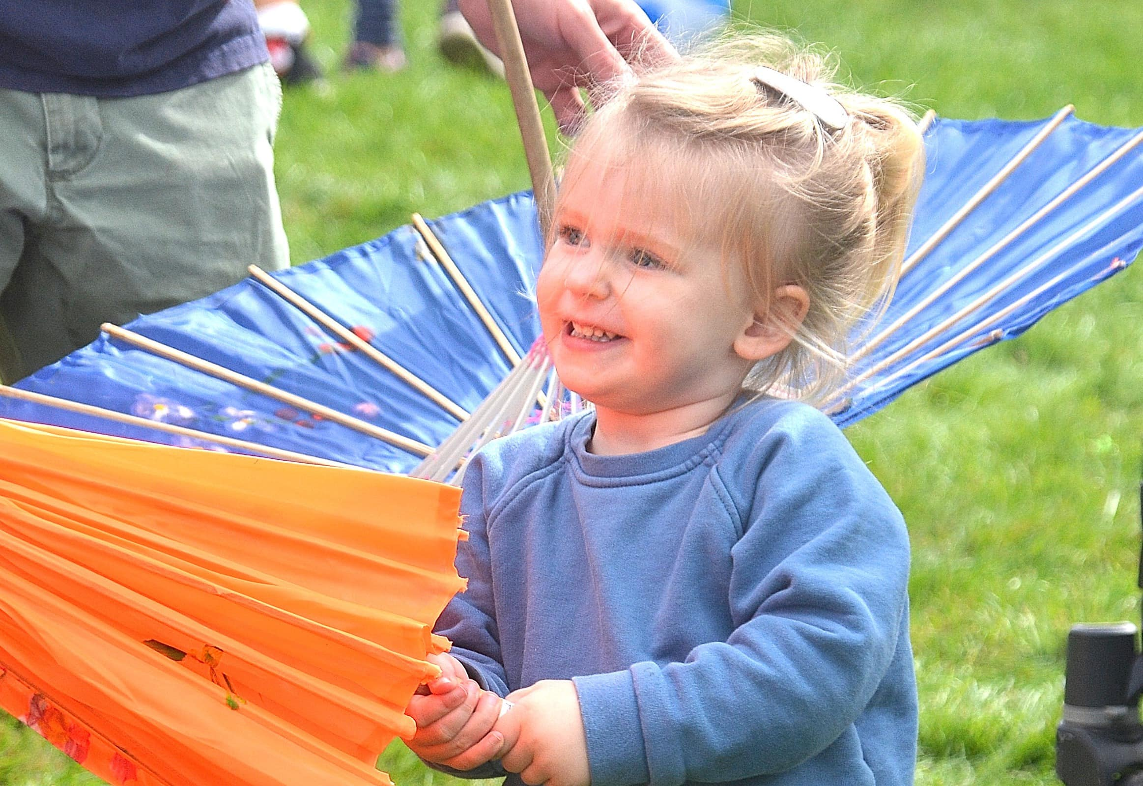 Gray Moore, 2, shops for a souvenir umbrella during the post-parade celebration at St. Mark's School field.