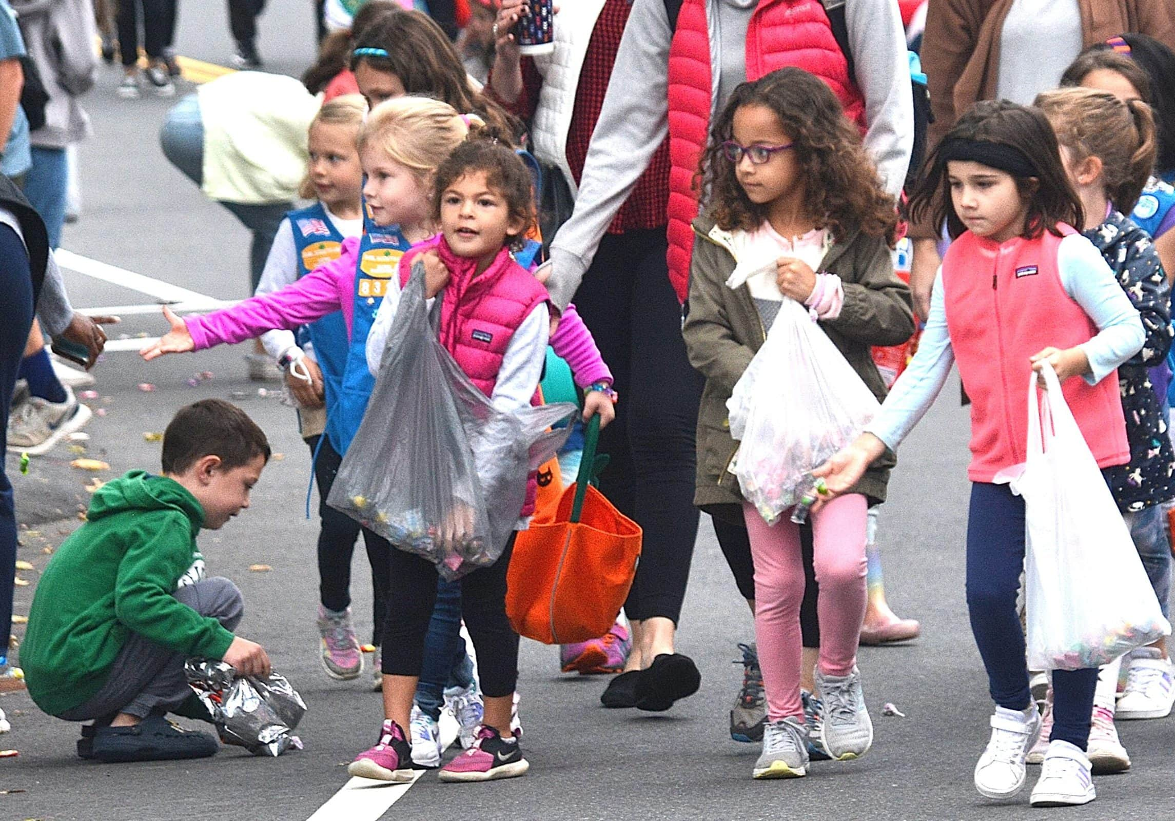 Members of Girl Scout Daisy troops toss candy to parade spectators on the sidelines.