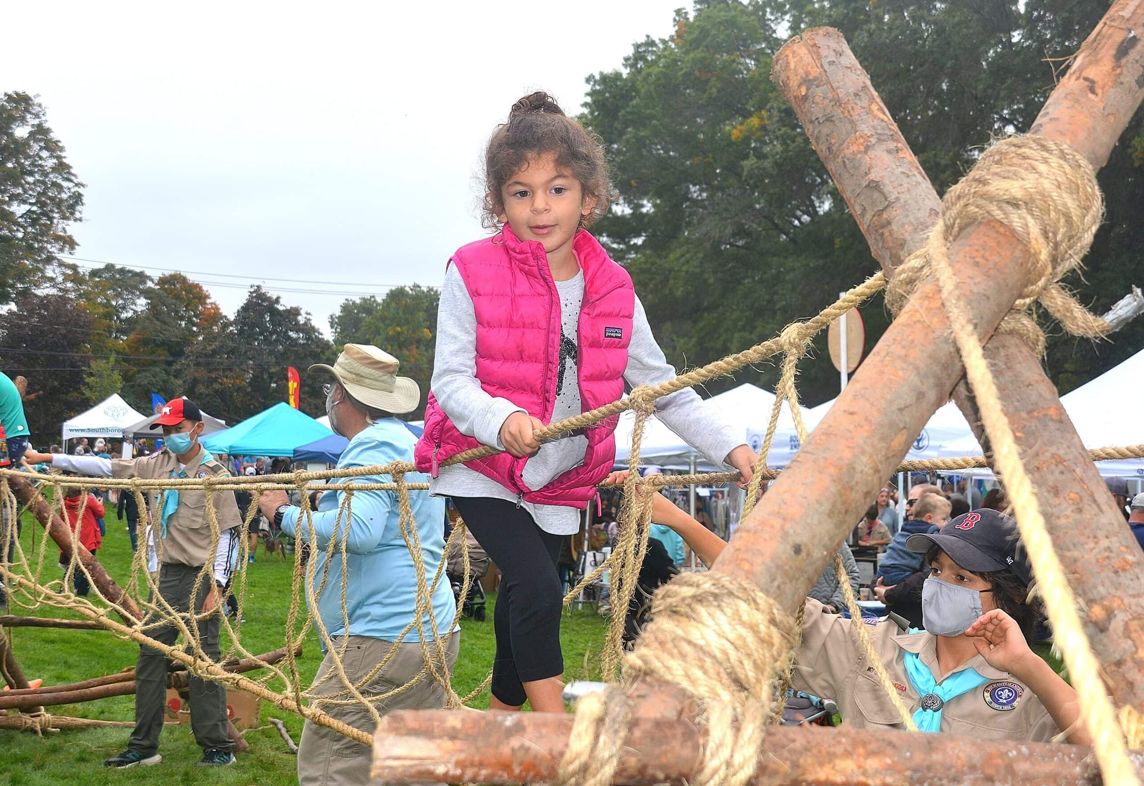 Kiley Werman, 5, reaches the end of the rope bridge provided by Boy Scout Troop 1.