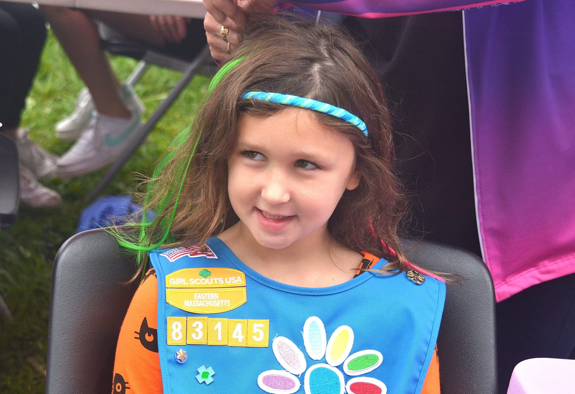"""Girl Scout Daisy Troop member Kelsey Rooney, 6, gets """"a mermaid hairpiece"""" at the booth of Diane Cournoyer Dance Center."""