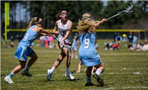 Algonquin Regional High School's Kendyll Finelli (#16, center) lets her shot fly against the defense of Medfield High School's , Grace Crowell (#14, left) and Nicole Brusa (#9, right).