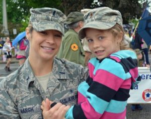 1st Lieutenant Brooke Marsh, a critical care nurse with the Air Force National Guard at Otis Air Force Base, holds her daughter Sawyer while listening to the program at the War Memorial. She marched in the Shrewsbury parade with fellow military members. Photo/Joyce DeWallace